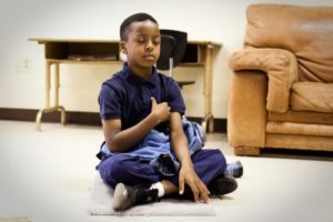 Little boy sat cross-legged on carpet with right hand on his heart