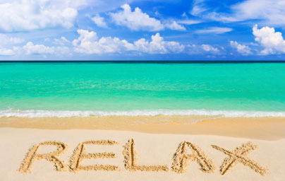 Image of RELAX written in golden sand with turquoise sea and sky