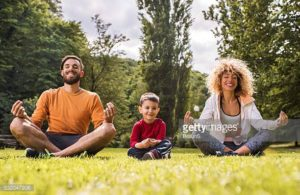 Man, woman and little boy all sat on grass practising mindfulness