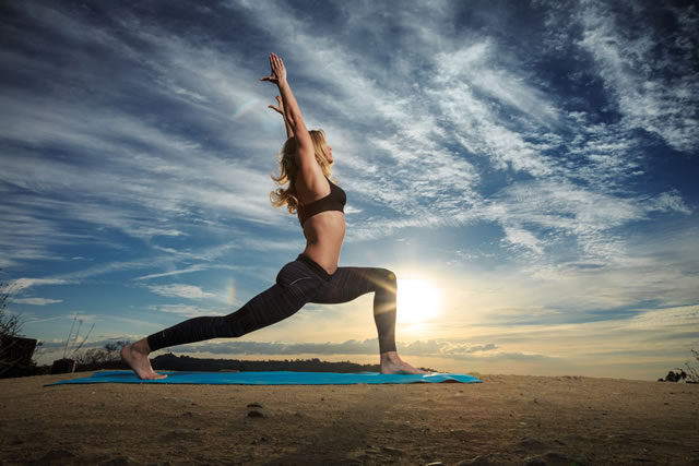 Woman stretching in warrior pose against backdrop of setting sun