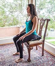 woman meditating sat on chair