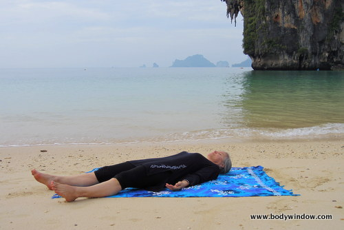 woman lying on blue towel on yellow sandy beach in corpse pose