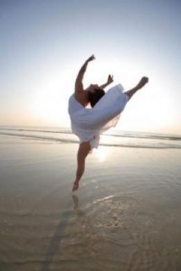 woman ballet dancer in white dress dancing on wet sand