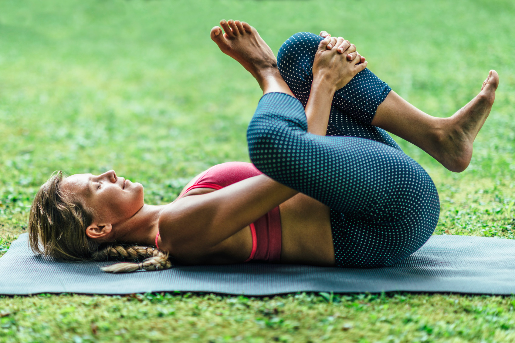 woman lying on yoga mat on grass in eye of the needle pose