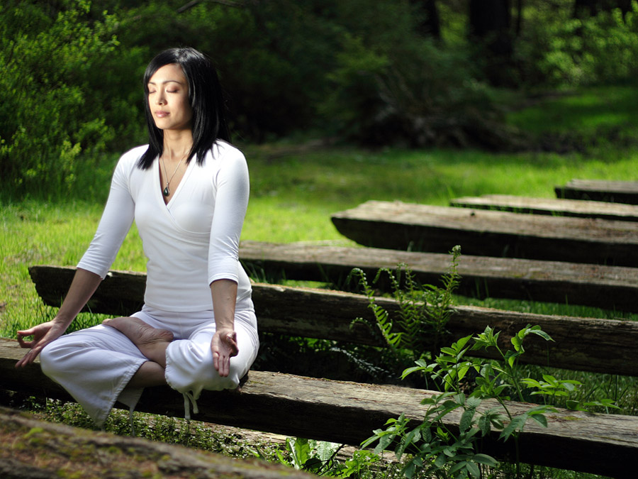 woman sat meditating in half-lotus yoga pose on wooden bench