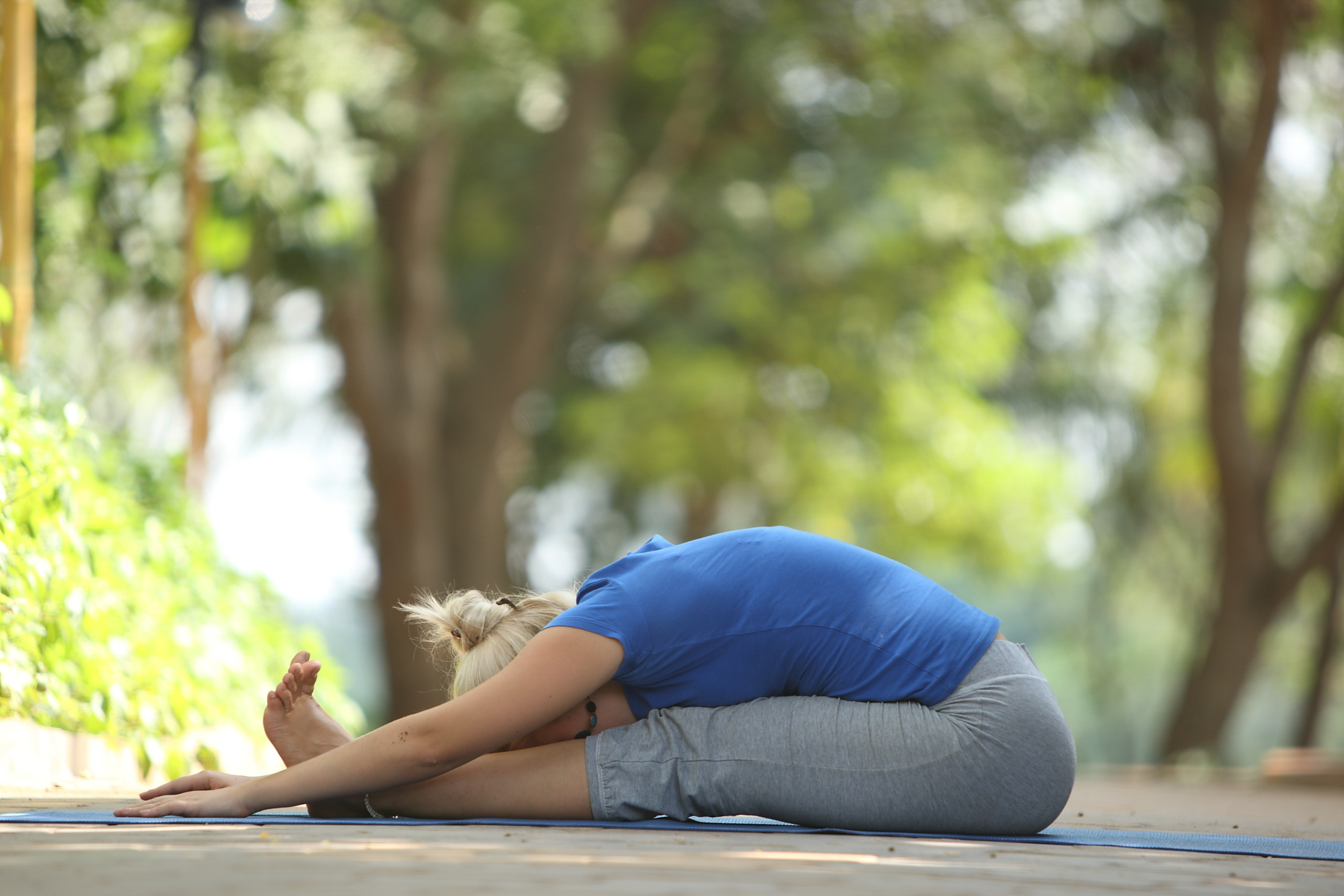 Woman on yoga mat in Seated Forward Bend Yoga Pose with trees in background