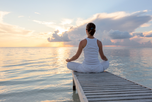 Meditating woman sat cross-legged on end of wooden pier staring across the water at sun-rise