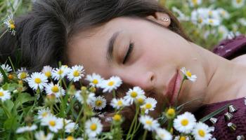 woman laid asleep on field of daisies