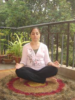 woman sat on balcony in sukhasana yoga pose in mindfulness meditation