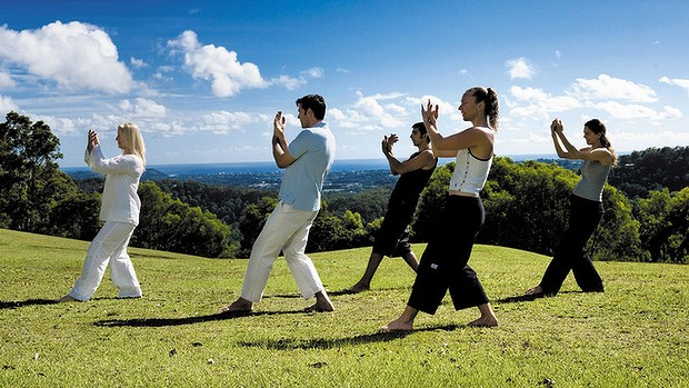 group of people practising tai-chi in field