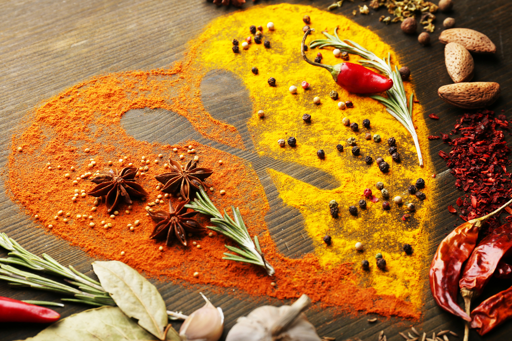 various spices and herbs laid out on wooden table in shape of heart