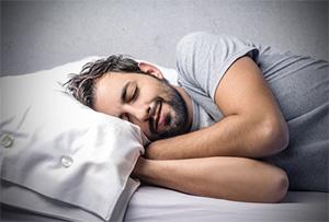 smiling man asleep in bed