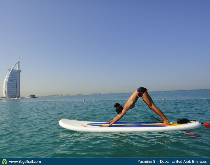 woman doing downward facing dog pose on sup board