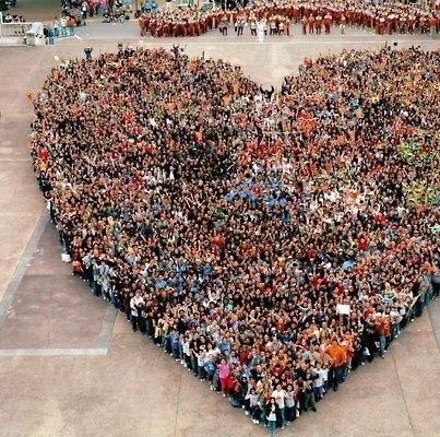 hundreds of people standing together creating huge heart shape
