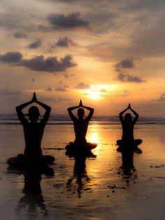three people sat on beach in yoga poses at sunset