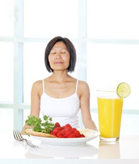 woman meditating before meal of salad and orange juice