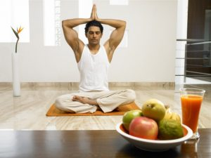 man in yoga pose in background with bowl of fruit in foreground with glass of fruit juice
