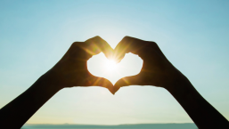 two hands forming heart shape with view of sun through the heart