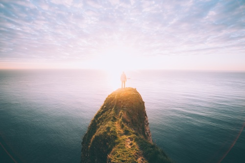 person standing on top of high rock surrounded by sea and silhouetted against the sun