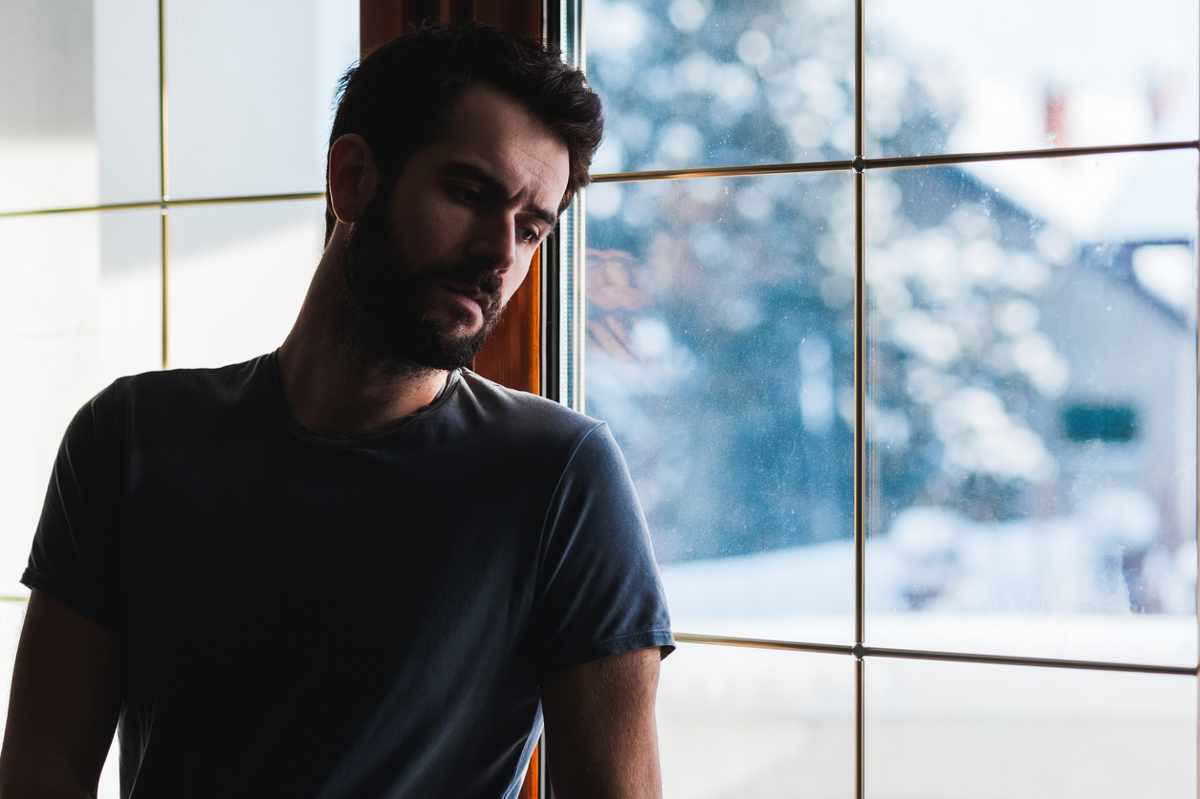 man suffering addiction leaning against window