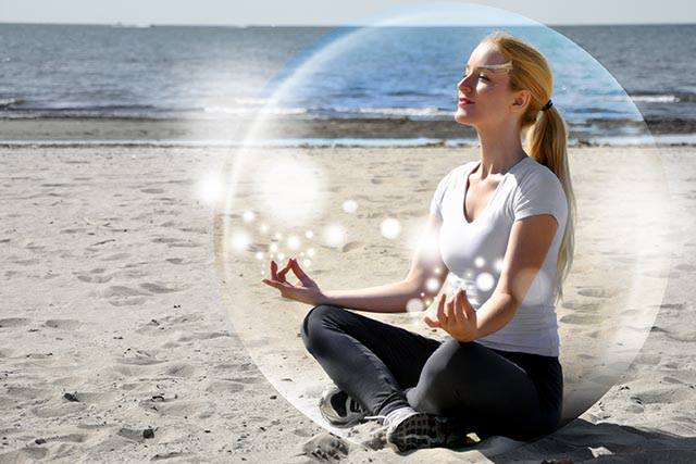 image of woman sat on beach in mindfulness meditation surrounded by huge bubble