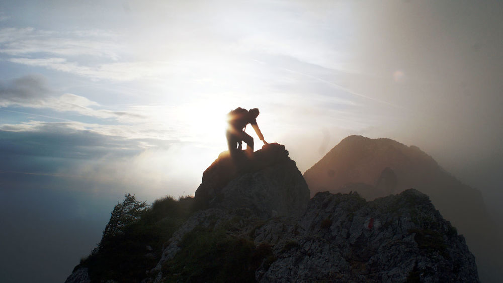 image of climber reaching top of mountain